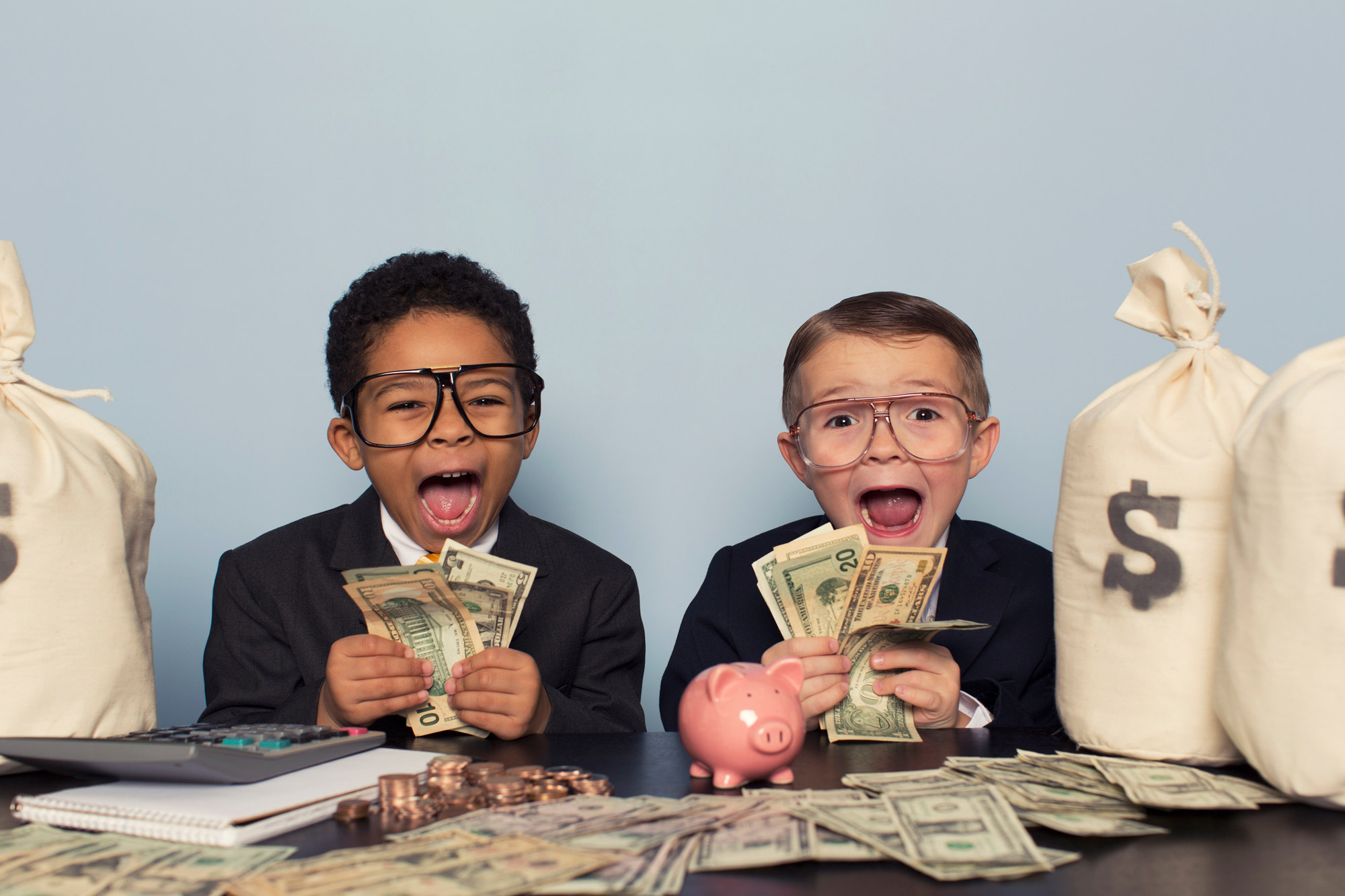 two kids surrounded by money