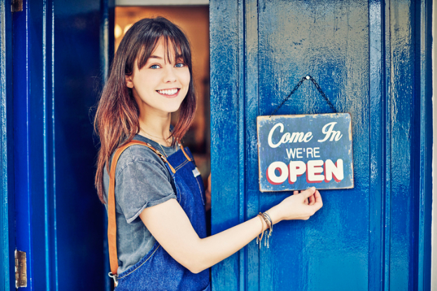 Woman with Come In We're Open Sign on Business Door